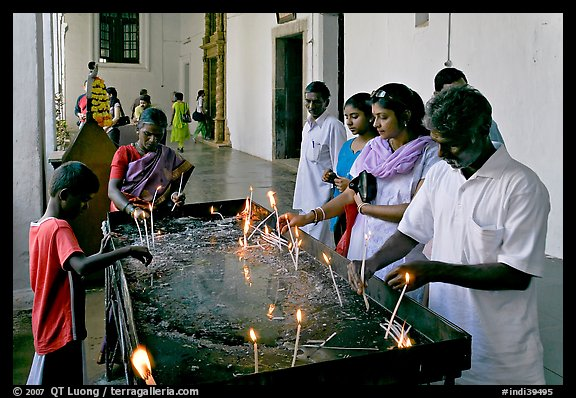 Indian people burning candles, Basilica of Bom Jesus, Old Goa. Goa, India