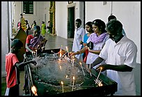 Indian people burning candles, Basilica of Bom Jesus, Old Goa. Goa, India (color)