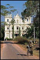 Man walking a bicycle in front of church of St John, Old Goa. Goa, India (color)