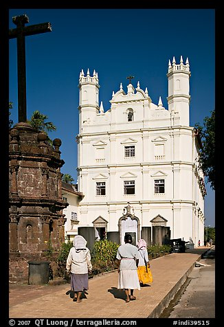 Women walking towards Church of St Francis of Assisi, afternoon, Old Goa. Goa, India (color)