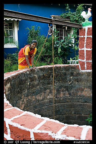 Woman retrieving water from well, Panaji. Goa, India (color)