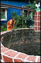 Woman retrieving water from well, Panaji. Goa, India