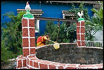 Woman retrieving water from well with blue house behind, Panjim. Goa, India