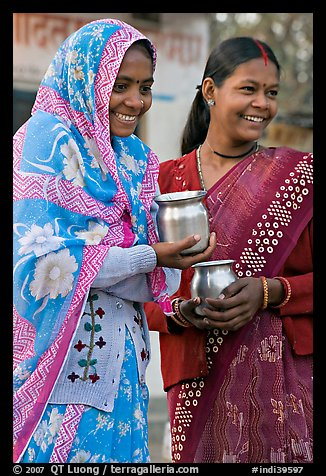Women with pots used for religious offerings. Khajuraho, Madhya Pradesh, India (color)