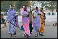 Hindu women walking in street with pots. Khajuraho, Madhya Pradesh, India