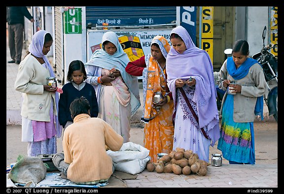 Hindu women purchasing offerings before going to temple. Khajuraho, Madhya Pradesh, India