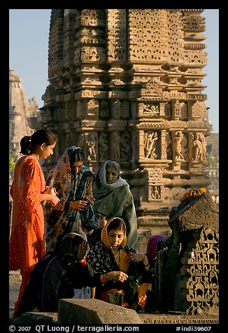Women offering morning puja  in front temple spire. Khajuraho, Madhya Pradesh, India (color)