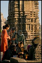 Women offering morning puja  in front temple spire. Khajuraho, Madhya Pradesh, India ( color)