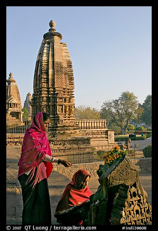 Women worshipping image with temple spire behind. Khajuraho, Madhya Pradesh, India