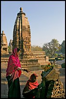 Women worshipping image with temple spire behind. Khajuraho, Madhya Pradesh, India (color)
