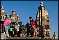 Women worshipping image with of Vahara and Lakshmana temples behind. Khajuraho, Madhya Pradesh, India