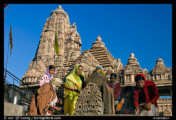 Worshippers making offering with Lakshmana temple behind. Khajuraho, Madhya Pradesh, India (color)