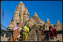 Worshippers making offering with Lakshmana temple behind. Khajuraho, Madhya Pradesh, India