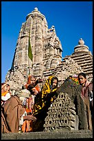 Hindu worshippers making offerings with Lakshmana temple behind. Khajuraho, Madhya Pradesh, India (color)