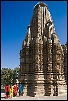 Women walking at the base of the sikhara of Devi Jagadamba temple. Khajuraho, Madhya Pradesh, India