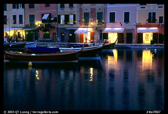 Light of shops reflected in harbor at dusk, Portofino. Liguria, Italy