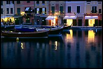 Light of shops reflected in harbor at dusk, Portofino. Liguria, Italy ( color)
