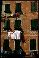 Typical terra cotta facade with hanging laundry and green shutters, Vernazza. Cinque Terre, Liguria, Italy