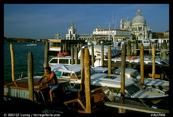 Water taxi driver cleaning out his boat in the morning, Santa Maria della Salute in the background. Venice, Veneto, Italy (color)