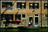 Resident stepping from his boat to his house,  Castello. Venice, Veneto, Italy