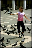 Girl playing with the pigeons, Piazzetta San Marco (Square Saint Mark), mid-day. Venice, Veneto, Italy