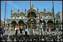 Children feeding flock of pigeon, in front of the Basilica San Marco, mid-day. Venice, Veneto, Italy