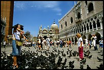 Visitors feeding  pigeons, Piazzetta San Marco (Square Saint Mark), mid-day. Venice, Veneto, Italy
