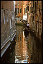 Gondola and reflections in a narrow canal. Venice, Veneto, Italy