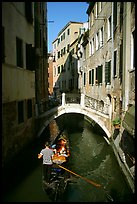 Gondola tour in a picturesque canal with bridge. Venice, Veneto, Italy