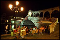 Outdoor cafe terrace,  Rialto Bridge at night. Venice, Veneto, Italy