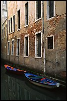 Small boats moored along a wall in a small side canal. Venice, Veneto, Italy