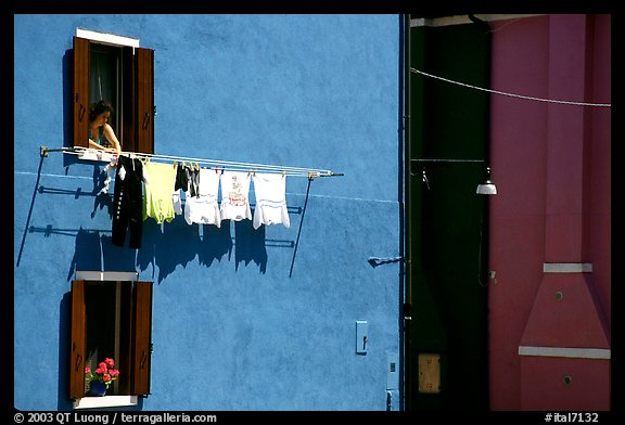 Woman hangs laundry to dry, Burano. Venice, Veneto, Italy (color)