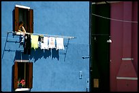 Woman hangs laundry to dry, Burano. Venice, Veneto, Italy