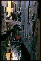 Pedestrians on a bridge over a narrow canal. Venice, Veneto, Italy