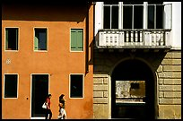 House facades with women walking. Veneto, Italy