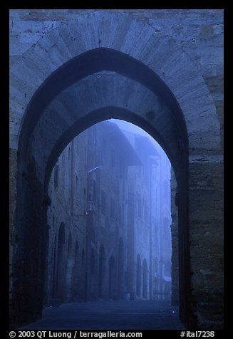 Arch at dawn in the fog. San Gimignano, Tuscany, Italy