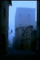 Street and medieval tower at dawn in the fog. San Gimignano, Tuscany, Italy (color)