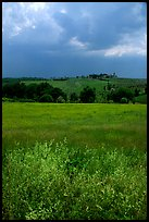 Field and distant village under storm skies. Tuscany, Italy