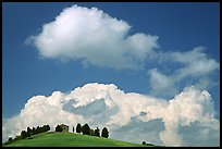 Fluffy clouds above ridge with cypress trees and house. Tuscany, Italy