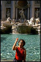 Tourist tosses a coin over her shoulder in the Trevi Fountain. Rome, Lazio, Italy