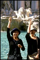 Asian tourists toss a coin over their shoulder into the Trevi Fountain. Rome, Lazio, Italy