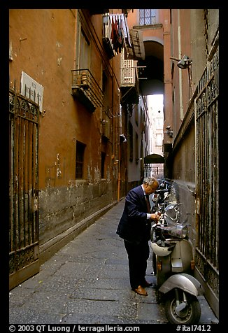 Man locking his motorbike in a side street. Naples, Campania, Italy (color)