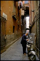 Man locking his motorbike in a side street. Naples, Campania, Italy ( color)