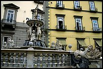 Fountain with man at balcony in background. Naples, Campania, Italy