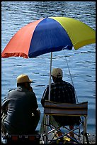 Men fishing under an colorful sun unbrella,  Agropoli. Campania, Italy