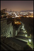 Path, wall, and city lights, Suwon Hwaseong Fortress. South Korea