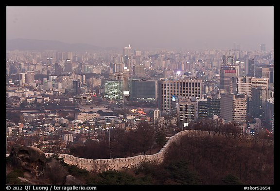 Old fortress wall and high-rises at dusk. Seoul, South Korea (color)