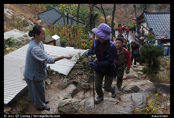 Woman giving sacred bread at Sangseonam hermitage, Namsan Mountain. Gyeongju, South Korea