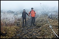 Couple hiking holding hands in fog. Jeju Island, South Korea ( color)