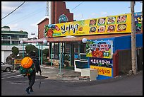 Haeneyo woman walking towards seafood restaurant. Jeju Island, South Korea (color)